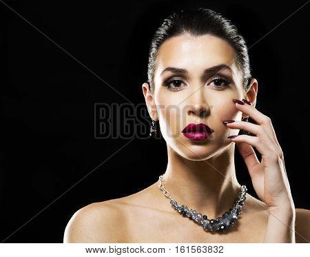 Beautiful Brunette With Dark Makeup Wearing Blue Jewellery