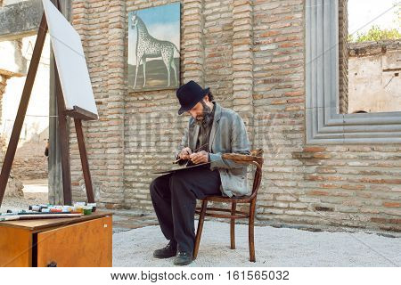 TBILISI, GEORGIA - SEP 25, 2016: Bearded artist similar to the popular Niko Pirosmani drawing paintings at the easel during the weekend on September 25, 2016. Tbilisi has population of 1.5 million people