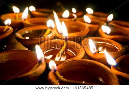 Shots of earthenware lamps filled with oil and with a cotton wick. These diyas are lit during diwali and other celebrations