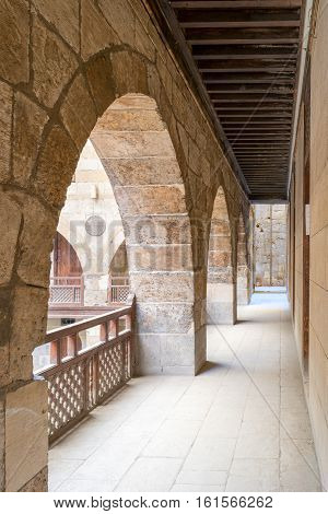 Angled view of one arch with interleaved wooden balustrades at the arcade surrounding the courtyard of a historic caravansary (Wikala), Medieval Cairo, Egypt