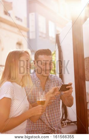 Laughing Couple With Cellphone And Beers