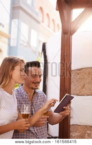 Millenial Couple Sharing A Touchpad And Beers