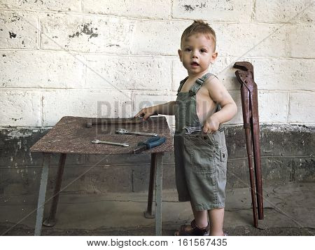 little boy with a wrench standing at the wall
