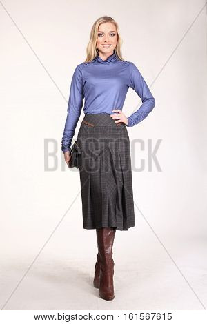 blond hair woman with straight hair style in blue blouse skirt high heel shoes going full body length isolated on white