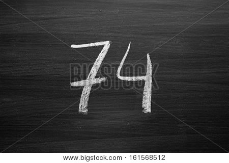 number seventy four enumeration written with a chalk on the blackboard