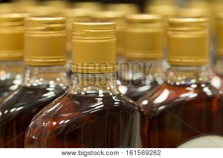 Top of plastic bottles with cognac or brandy standing in the liquor store. From the side