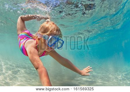 Happy baby girl in snorkeling mask dive underwater with fun in sea pool. Healthy lifestyle people water sport outdoor adventure swimming lessons on summer beach family holidays with child