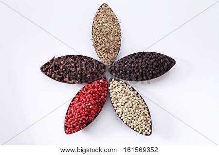 five different spices in oval shape container form a flower pattern