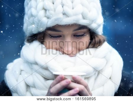 Beautiful young woman wearing white merino wool hat and scarf enjoying the fresh winter morning outdoors. Skin Care Lip care care of the eyelashes in the winter season.