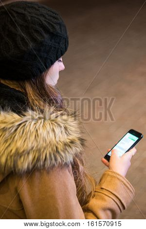 Woman texting on smart phone at night in winter