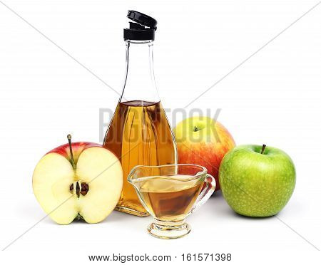 The open transparent full bottle and cup of Apple cider vinegar and a few different varieties of apples isolated on a white background.