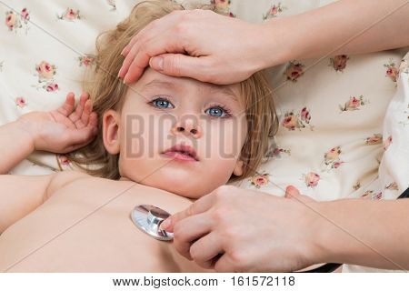 Female hand holding a sick child forehead and listening to his stethoscope
