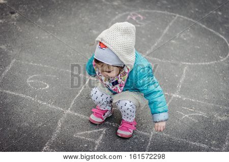 small and pretty girl playing hopscotch in the park