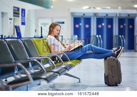 Beautiful Young Tourist Girl With Backpack And Carry On Luggage In International Airport