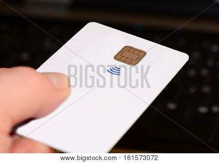 Hand holding and paying with a all white contactless credit card.