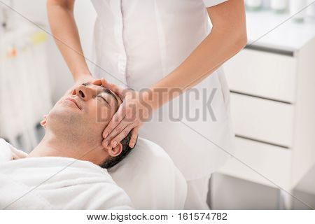 Relaxed man is having treatment at spa. Masseuse is standing and pampering his head