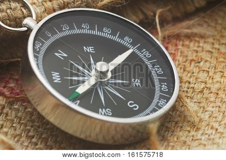 a isolate metallic compass on gunny sack