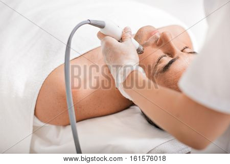 poster of Professional beautician is rejuvenating male face by cavitation laser apparatus. Man is lying on massage table and relaxing