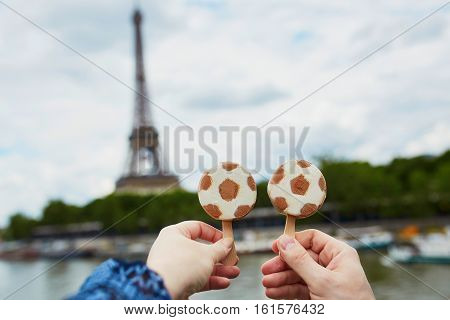 Couple In Paris Holding Ice Cream In Form Of Soccer Ball In Front Of The Eiffel Tower In Paris