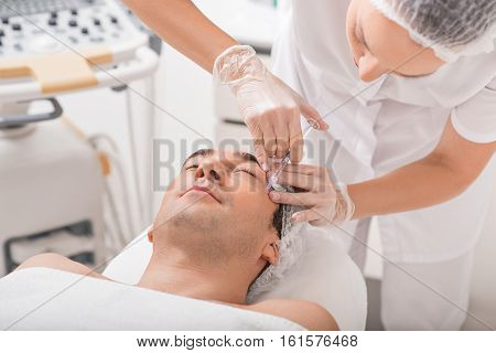 Professional female cosmetologist is rejuvenating male wrinkles by anti-aging liquid. She is holding syringe near patient eye area