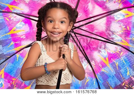 Cute african american small girl smiling and holding a huge colorful umbrella