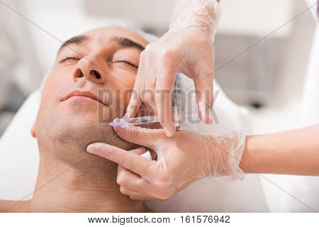 Close up of skillful beautician hands preventing facial skin aging. She is injecting botox into male chin
