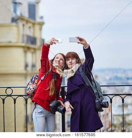 Two Cheerful Girls In Paris Taking Selfie Using Mobile Phone On Montmartre