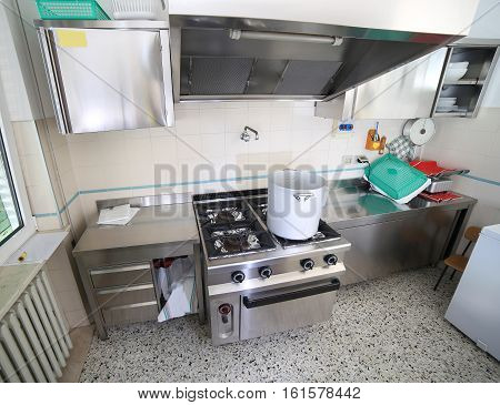 Inside the kitchen of a kindergarten with big stove and an aluminum pot