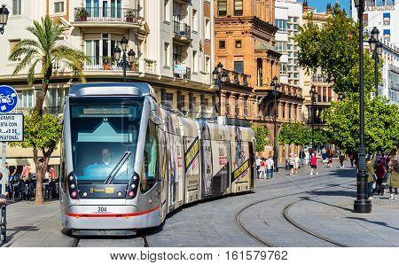 Seville, Spain - November 1, 2016: MetroCentro tram on Avenida de la Constitucion. These trams are able to run without overhead wire