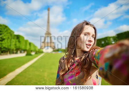 Woman tourist at Eiffel Tower smiling and making travel selfie. Beautiful European girl enjoying vacation in Paris France