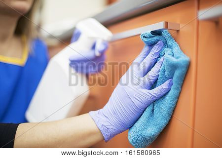 Woman at work professional maid cleaning in dental office