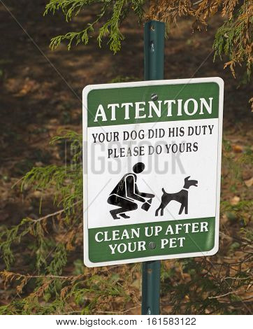 Close up of a sign urging dog owners to clean up after their pets
