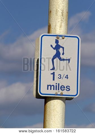 A sign displaying the symbol of a person running and a mileage distance of one and 3/4 miles