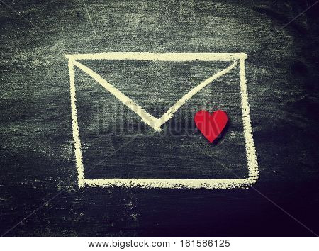 Painted Envelope with Red Heart on a Chalkboard. Top view. Love; Message or Love Message Concept