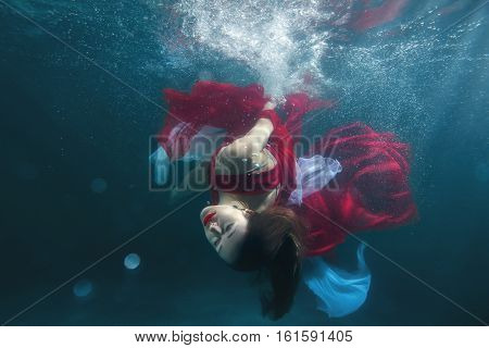In the pool underwater dancing girl she in a red dress.
