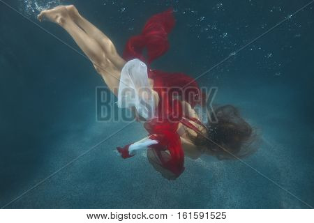A woman in a red dress swimming underwater in the pool.