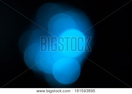 Blue blurred lights, bokeh effect. Real photo background. Isolated on black