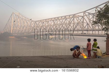 KOLKATA, INDIA - DECEMBER 11, 2016: Street kids keep warm on a cold foggy winter morning at Mallick ghat near Howrah bridge at the bank of river Hooghly.