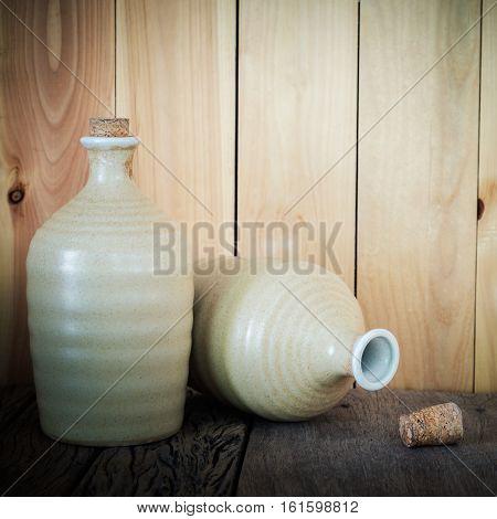 Still Life Of Sake Bottles With Light On Wood Background.