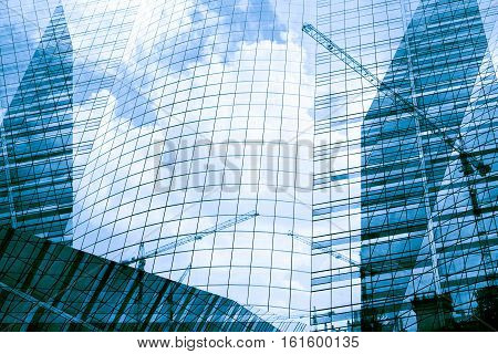 Reflection Of Tower Cranes Building Construction On Building Mirror. Abstract Background.