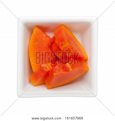 Slices of papaya in a square bowl isolated on white background