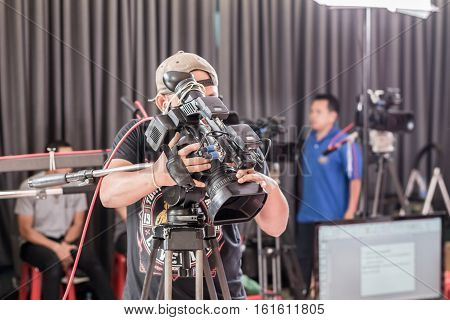 Man Use Digital Video Camera With Lens Equipment In Professional Media Studio