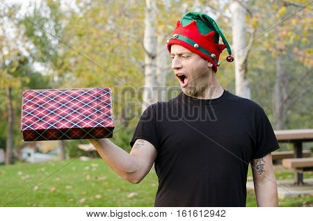 Man with a surprise gift wearing a Christmas hat!