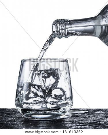 Pouring alcohol into a glass. Monochrome picture.