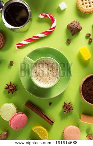coffee cup and beans at green paper background