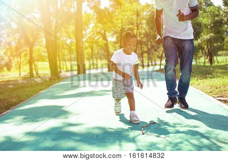 African American Boy Walking And Playing With Dad In Green Park Outdoor