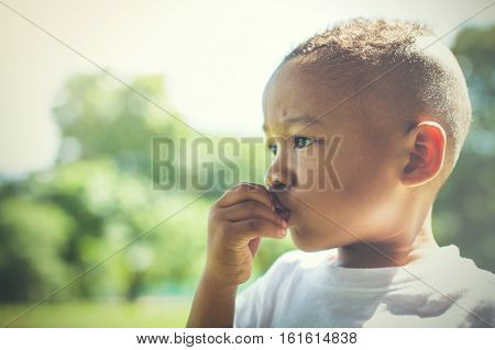 Mixed race between Asian and African American kid thinking and being curious outdoor