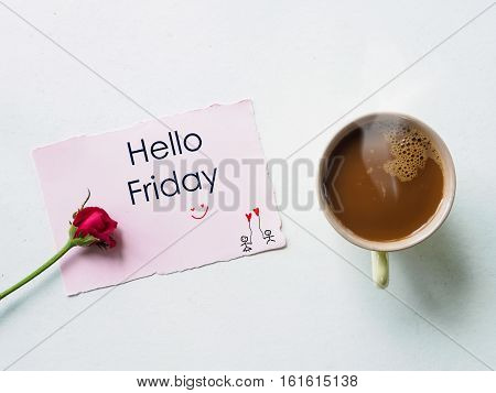 Hello Friday message coffee mug with red rose flowers on white table happy Friday concept