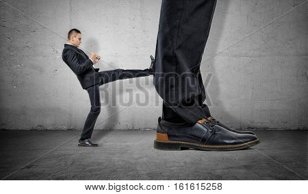 Tiny businessman kicking huge legs of another on the gray concrete background. Business rivalry. Confident behaviour. Career growth.
