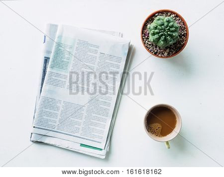 Break time of coffee cup cactus and newspaper workplace on white desk Flat lay